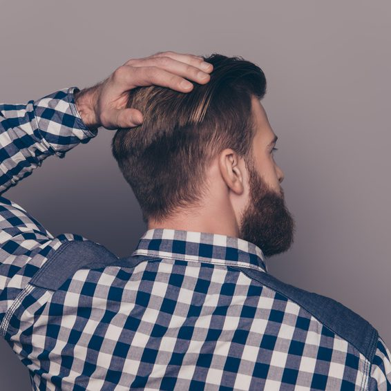 Back-view of stylish   handsome young man touch his hair with hands