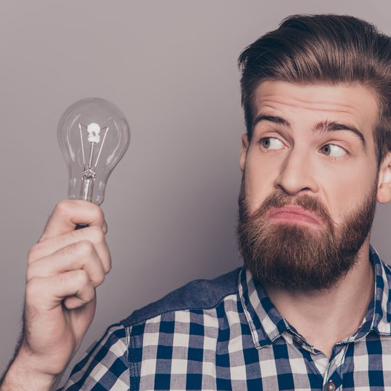 Portrait of young genious man with idea holding lamp